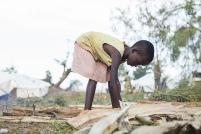 A young girl bends down to pick up firewood in a refugee camp