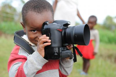 Boy in Rwanda holds camera