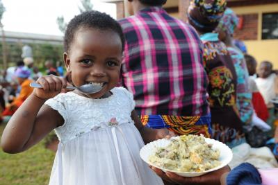 A young girl in a white dress feeds herself a healthy meal from a plate with a spoon