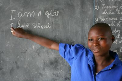 Girl in Rwanda in school writes on black board