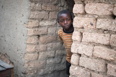 Boy in Rwanda looks out of his latrine in rural area