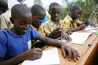 Boy and girl students in Rwanda wearing uniforms writing on desks at school