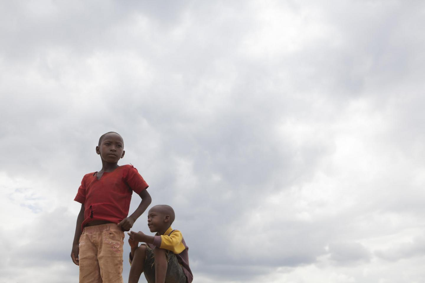 Two Burundian refugee boys survey Mahama Camp from atop a mound of dirt.