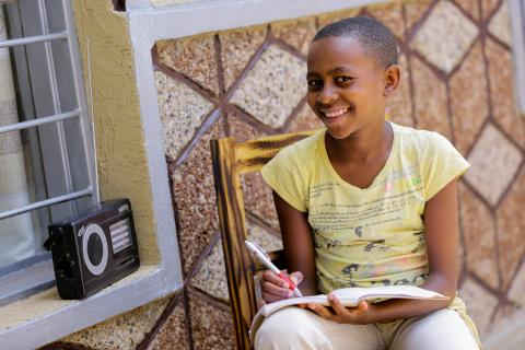 Umuhoza Dative, 11, sits at home near her radio holding her pen and notebook. Like many primary students, she is now learning from home due to COVID-19 related school closures, listening to radio lessons developed with support from UNICEF.
