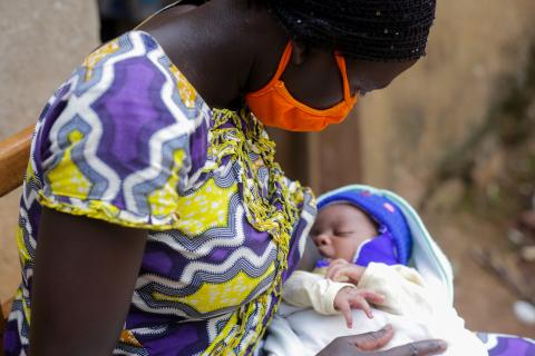 During COVID-19 in Rwanda, a mother breastfeeds her baby while wearing a mask.