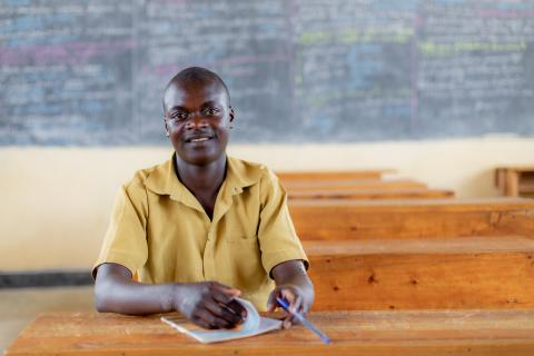 Marcel, 16, smiles inside his classroom in Rwanda. After dropping out two years ago, Marcel has returned to school to become top of his class and will graduate from primary school this year.