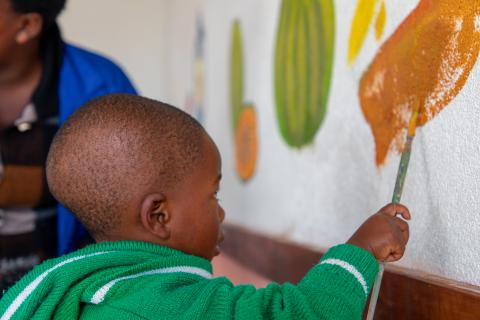 A little boy at the Rutsiro Tea Plantation ECD centre paints a mural of fruits with UNICEF and local artists.