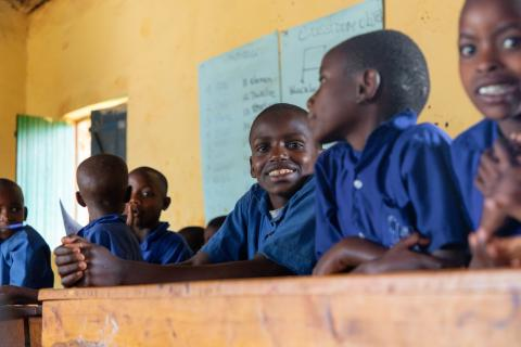 Hodari, centre, sits with fellow primary students in his classroom in Rwanda. Hodari learns under a UNICEF supported inclusive education programme to integrate children with disabilities in regular classrooms.