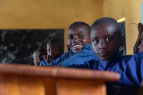 14-year-old Hodari, centre, sits between classmates inside a primary classroom at UNICEF-supported school G.S. Nyagahandagaza in Rwanda.