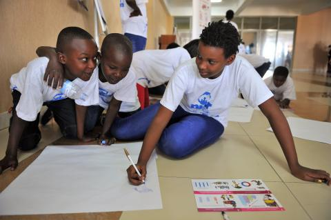 Three children in Rwanda sit together and draw while discussing data