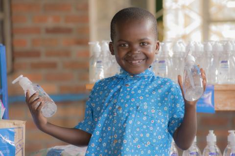 Young Vincent, 7, poses with new bottles of alcohol-based sanitizer, delivered to his care facility by UNICEF.