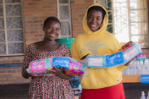 Marie, 20 (left), and Claudine, 23 (right), hold packages of new menstrual pads delivered by UNICEF.