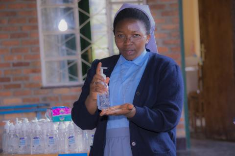 Sister Priscah Uwamahoro, Coordinator of Centre Saint Vincent, uses a new bottle of alcohol-based sanitizer provided by UNICEF. She has been caring for children with disabilities at this institution for 5 years.