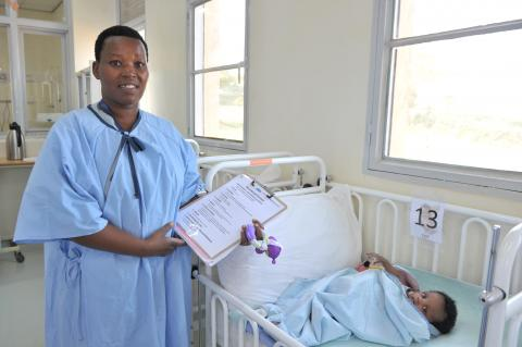 Jacqueline Mukawiringiye, Head Nurse in the neonatology ward at Rwanda's Gahini Hospital, stands in her scrubs wit ha clipboard next to the bed of a prematurely born baby, now recovering and in good health.