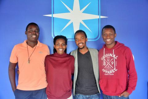 Four Rwandan youth stand together and smile at camera