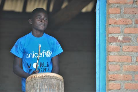 Child in Rwanda on World Children's Day plays the drums wearing a UNICEF shirt.