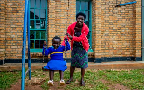 Olive Dukundimana pushes her daughter Ikaze on the swings at the UNICEF-supported Gikomero Early Childhood Development Centre in Rwanda.
