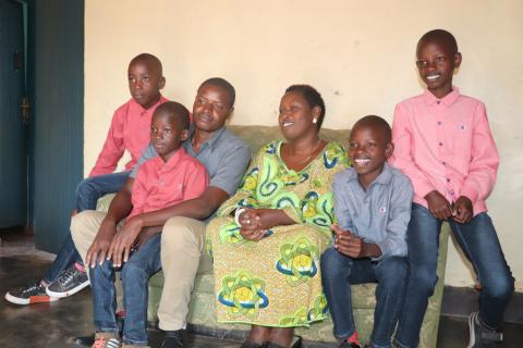 Manzi smiles with his new brothers and parents. Thanks to UNICEF-supported social workers, Manzi found a loving family and was able to move out of his orphanage.
