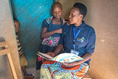 A Rwandan 'Inshuti z'Umuryango' volunteer sits with a child to discuss educational materials on child protection.