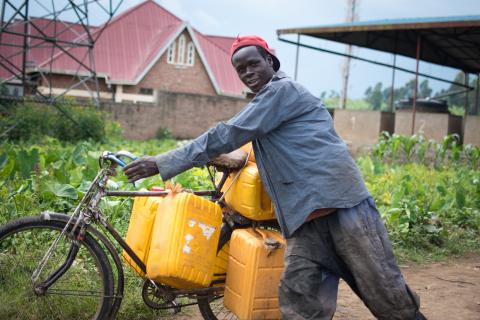 Man in Rwanda carries water in jerry cans on a bicycle