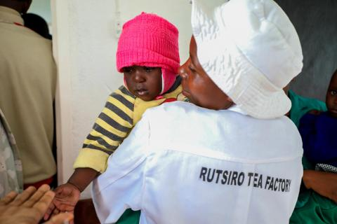 A caregiver at the Rutsiro Tea Plantation ECD centre holds a baby in a yellow striped shirt