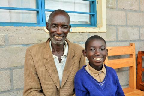 Boy with disability in Rwanda sits with father at school
