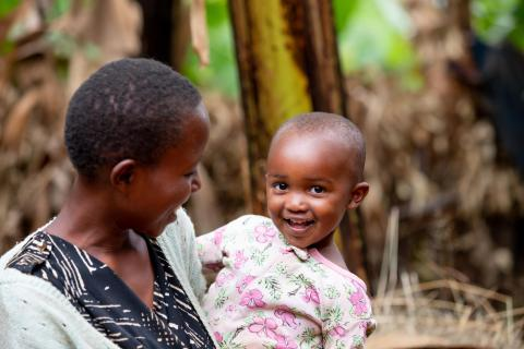 A teenaged mother in Rwanda holds her smiling baby girl