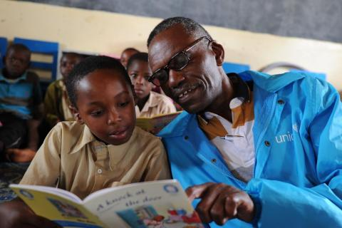 Cyriaque Ngoboka, UNICEF Communication Specialist, reads a book with a young boy at a primary school in Rwanda.