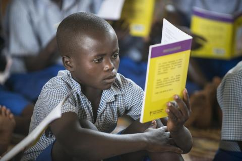 Jerome Niryayo reads in the reading room at Kanyina School in Nyarugenge, Rwanda.