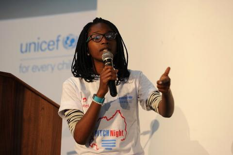 Girl teenager in Rwanda stands on stage pitching business idea