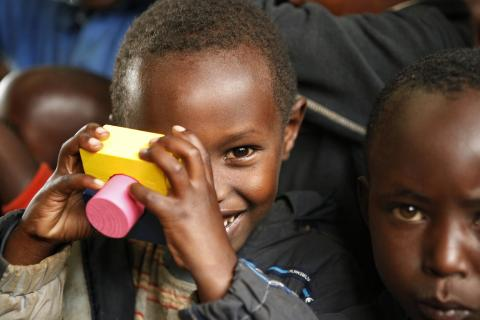 Small boy in Rwanda plays with toy blocks in early childhood development center