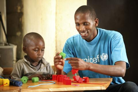 A UNICEF staff member plays with a child