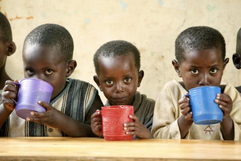 Three children at a UNICEF supported early childhood development centre sip porridge for breakfast.