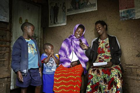 Mother and two children in Rwanda with community health worker using RapidSMS system