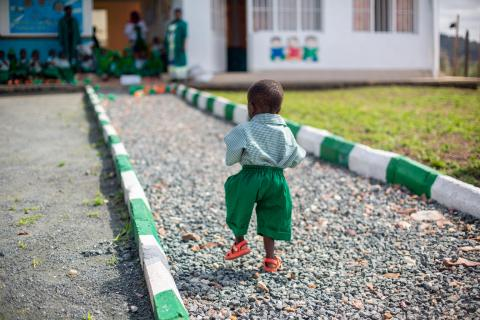 At the Rutsiro Tea Plantation early childhood development centre, David walks slowly back towards his friends while they drink milk.