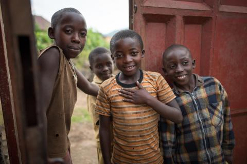 Four children in Rwanda smile at the entrance to their gated compound home.
