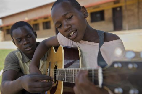 Young teenage boy in Rwanda plays guitar under a tree while another adult helps him.