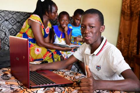 "Alain, 12, learning from home in Côte d'Ivoire. ""I like to study at home, and it's easy to follow classes online. Of course I miss my friends, but it's also nice to spend more time with my dad at home."""
