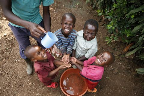 Several small children stand around a bucket of water while an adult male pours water from a cup so they can wash their hands.