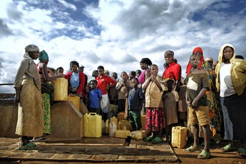 Several people crowd around a rural water tap with jerry cans, waiting their turn to fill them