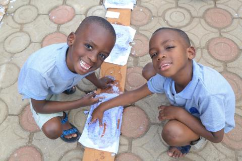 Two young Rwandan boys, sons of UNICEF staff Jean Claude Rukundo smile with their new papier mache creations the made during COVID-19.
