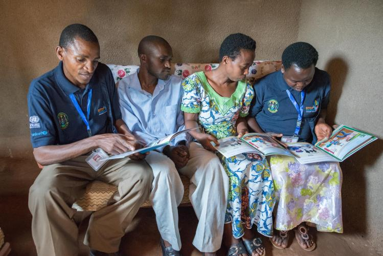 "One of Rwanda's ""Friends of the Family"" child protection volunteers visits a family in Rwamagana District and reads some educational materials with the parents."