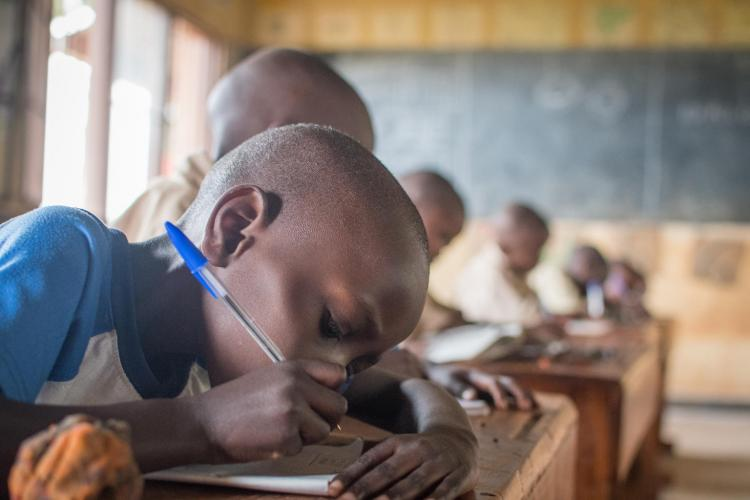 A boy in primary school in Rwanda writes studiously at his desk.