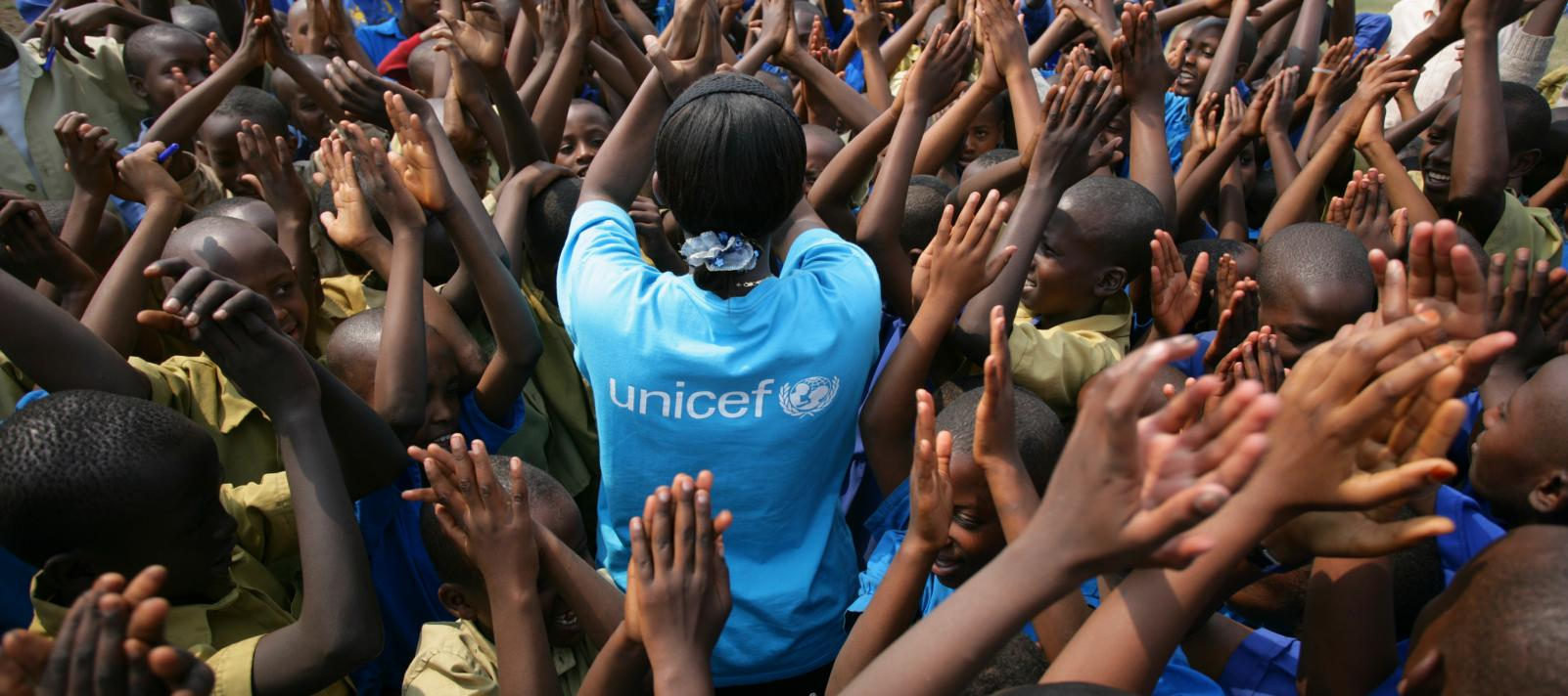 Children and UNICEF employee clap hands at school in Rwanda