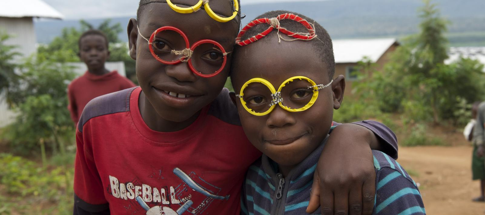 Two young boys smile at the camera wearing homemade glasses