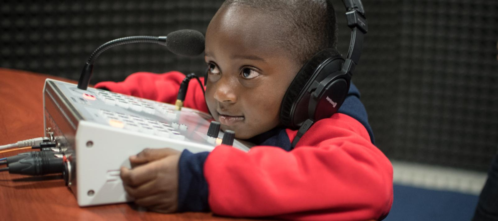Small boy in Rwanda radio station with headphones