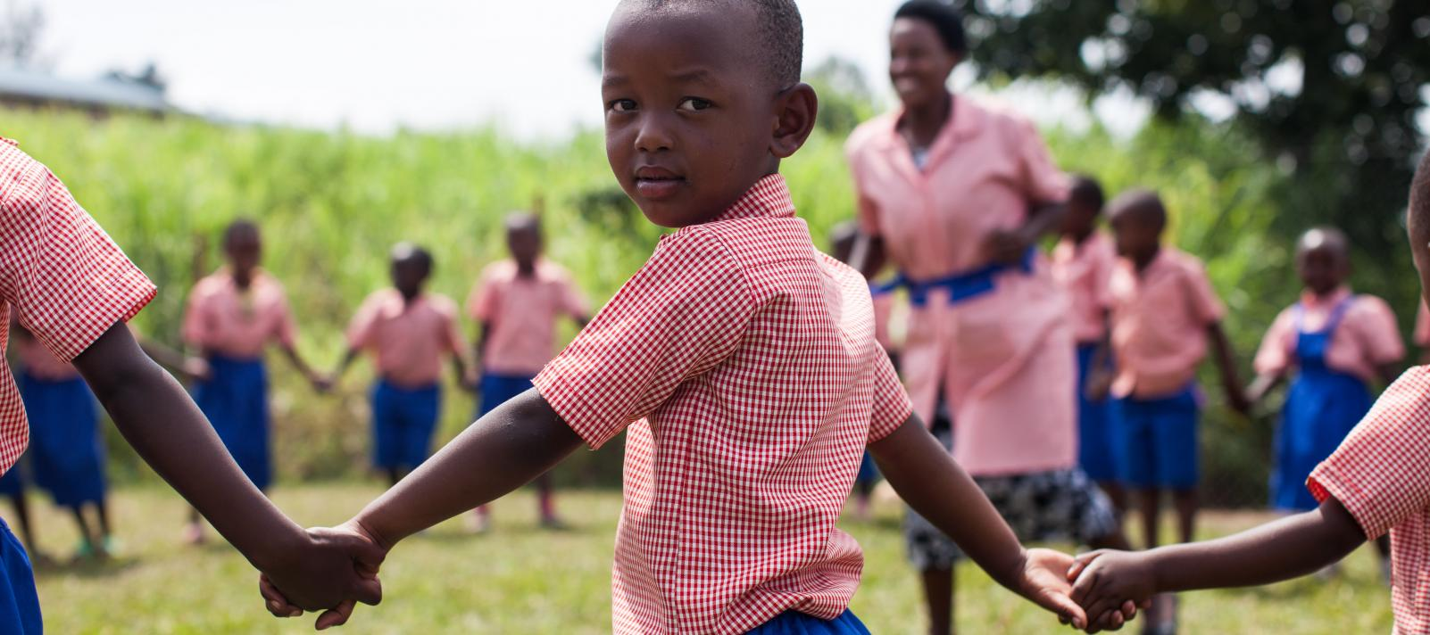 Preschool child in Rwanda holds hands with classmates