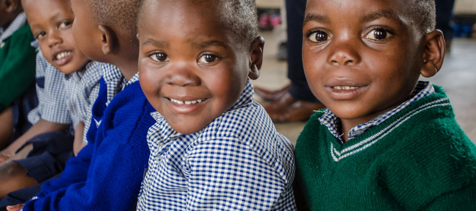 Three young children smile together in a pre-primary school