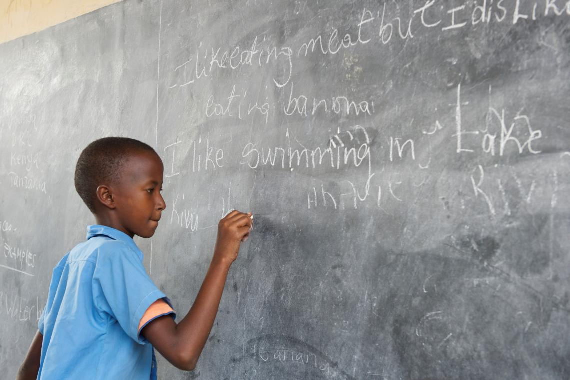 Young Burundian refugee boy in Rwanda at school writes on blackboard