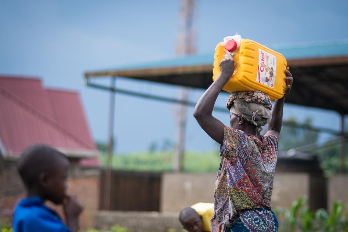 A woman carries a yellow jerry can full of water on her head